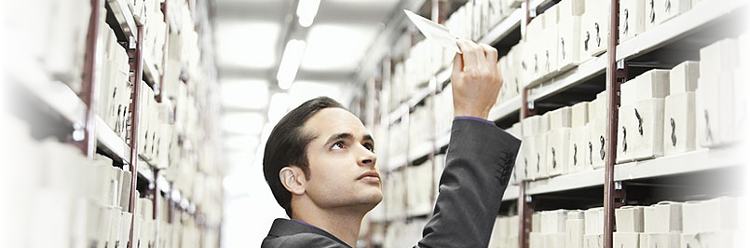 Image of a man looking at a microfiche, with shelves that are full of microfiche in the background. The image relates to this blog article, as the article describes how capturing the data from a microfiche can save and protect the data. We offer a service where we capture and convert your microfiche data to a digital file with our microfiche scanning services in London and throughout the UK.