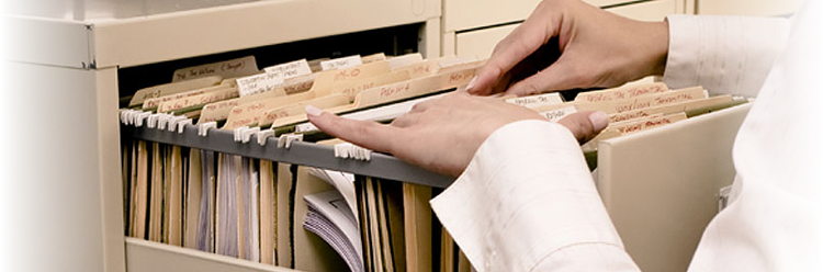 An image of a person searching through documents in a filing cabinet. The image relates to the blog article, as the article gives the user information on how scanning docuemnts to a digital file can save time in various departments in all types of organisations in London and all over the UK. Our document scanning services in London and the UK offer a cost effective solution to help organisations go paper free.